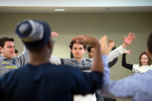 Shean Krolicki, center, Mohamad Bazzi, left, and William Royster, facing away from the camera, warm up during a session on how to use gestures, intonation and other techniques to enhance vocal performance.