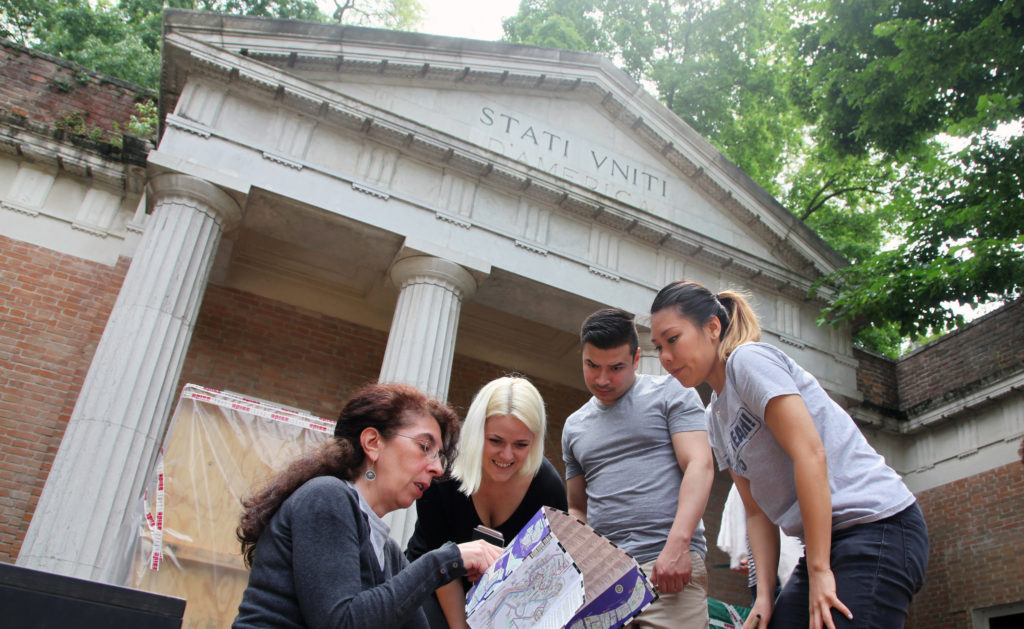 Students and faculty members from Taubman College will represent the U.S., Canada and Kuwait world's top architecture show. From left: U-M Taubman fellows Kristen Gandy, Ramon Hernandez, and Diana Tsai map out installation plans in front of the U.S. pavilion with Chiara Barbieri, Peggy Guggenheim Collection U.S. Pavilion manager, a palladian-style structure built in 1930 by the then well-known architects William Adams Delano and Chester Holmes Aldrich. It is located within the Castello Gardens that house all the national pavilions of the Venice Biennale. Photo by Salam Rida.