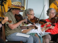 Fiddlers participating in a workshop for beginners at the Oldtime Fiddlers Convention in Hillsdale, MI.