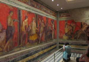 A visitor takes a photo of a large-scale watercolor representation of the famous Villa of the Mysteries murals from ancient Pompeii at the U-M Kelsey Museum of Archaeology.