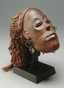 Artist unrecorded, Chokwe peoples, Angola, the Democratic Republic of the Congo and Zambia, Pwo (woman) mask, ca. 1890, wood, tukula powder, clay, string, metal, fur, snake-skin, cloth, chicken foot, tax token, button. Photo courtesy U-M Museum of Art.