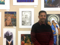 Reuben Kenyatta standing in front of artwork at the Prison Creative Arts Project exhibition at the Duderstadt Gallery.
