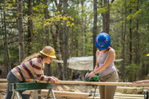 Students make a cut using a circular saw.