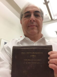 Russell Taichman holds a book detailing the 1864 Hall Arctic Expedition.