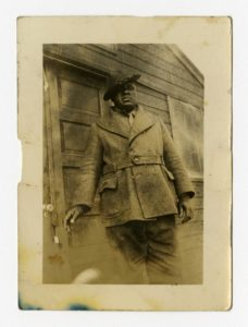Dressed in a heavy coat and hat, a man reaches for a doorknob to a cabin. Courtesy of the University of Michigan Bentley Historical Library.