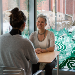 Christina Olsen, director of the U-M Museum of Art, chats with a student during her open office hours. Photo by Dave Lawrence.