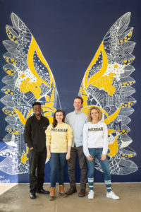 Graduating students from U-M Social pose in front of the new mural on the corner of E. William and Maynard. Photo by Scott Soderberg, Michigan Photography