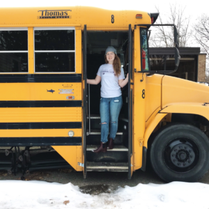 Tori Essex stands inside her school bus converted living space.