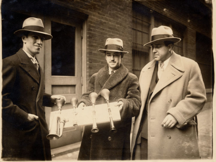 """GeorgeGershwin (left), JamesRosenberg, percussionistforCincinnatiSymphony (center),andtenorRichardCrooks (right),pose with taxi horns from """"An American in Paris"""" on February28,1929.PhotocourtesytheIra&LeonoreGershwinTrusts."""