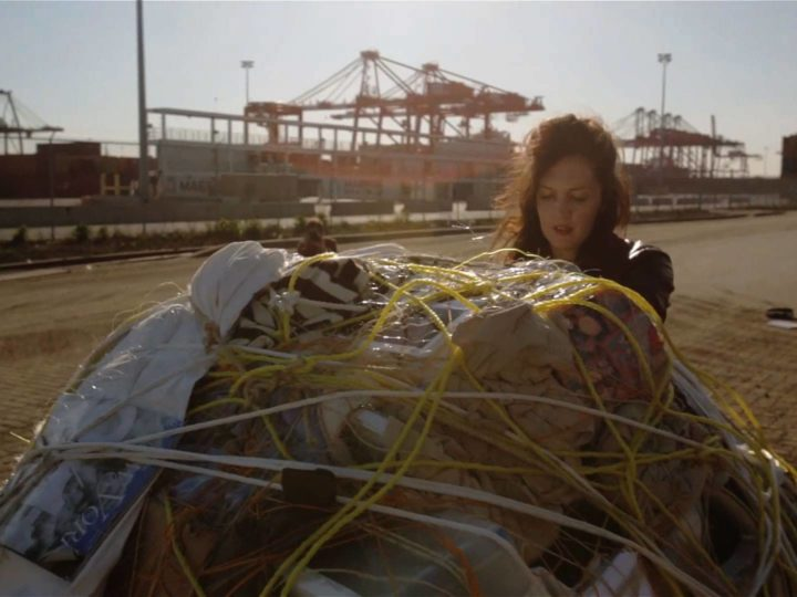 Artist Mary Mattingly pushing a sculpture of her personal belongings at the Port Newark Container Terminal. Photo courtesy ART21.