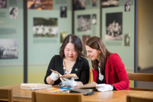 "Liangyi Fu, U-M Chinese studies librarian (left), and Emily Wilcox, U-M assistant professor of Asian languages and cultures (right), look at photos and artifacts from the ""Pioneers of Dance"" collection at the U-M Asia Library. Photo by Eric Bronson, Michigan Photography."