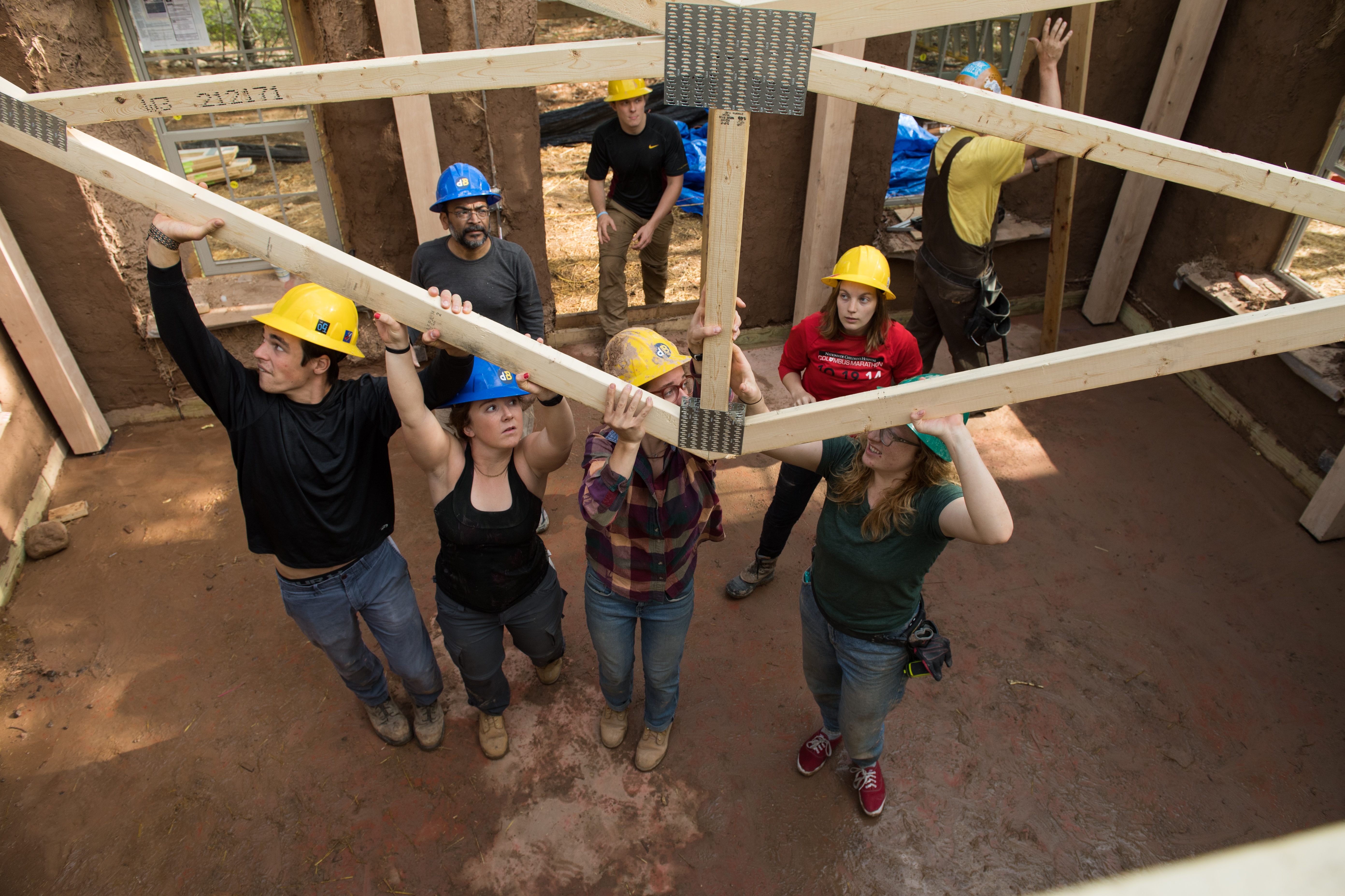Students raise the roof on the straw bale building.