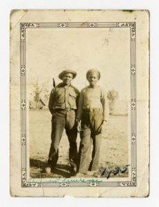 Two men stand together in a field, both dressed for work, in the background stand rows of tents and trees. Courtesy of the University of Michigan Bentley Historical Library.