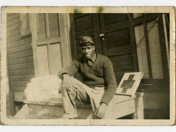 Seated near a medic cross propped against a doorway, a man dressed in casual wear smiles for his photograph. Courtesy of the University of Michigan Bentley Historical Library.