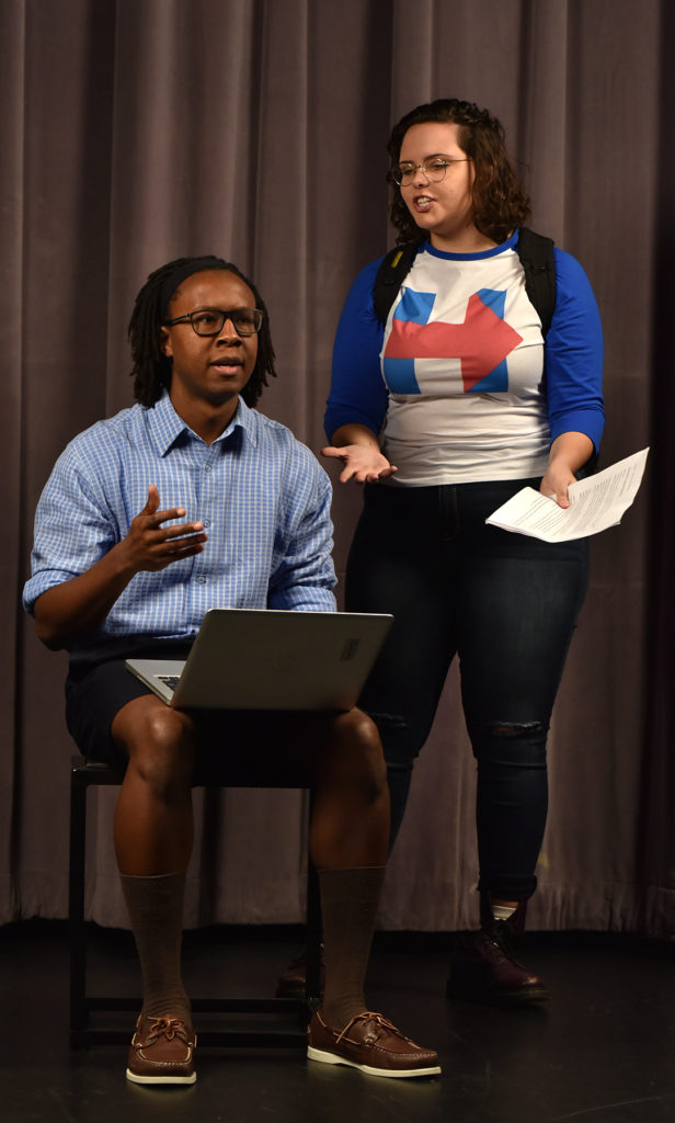 "Eddie Williams, Jr. as Justin (left) and Kathleen Taylor as Toria (right) discuss her newspaper article in the U-M School of Music, Theatre & Dance production of ""Blood at the Root"" by Dominique Morisseau. Photo by Peter Smith Photography."
