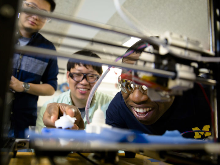 Molong Duon and Deokkyun Yoon, both mechanical engineering PhD students, and Chinedum Okwudire, associate professor in mechanical engineering, examine the effectiveness of their new, faster 3D printing algorithm. Photo: Evan Dougherty, Michigan Engineering