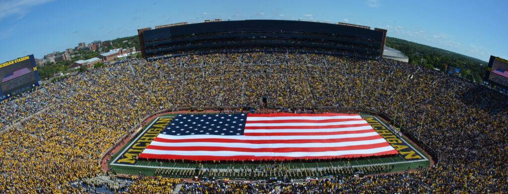 Michigan Marching Band at a halftime show with giant American Flag at Michigan Stadium