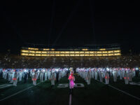 """Field level view of illuminated Michigan Marching Band Halftime Show on September 11, 2021. Drum Major on the side-line of the field looking out at the """"We Remember"""" 9/11 20th Yeah Anniversary Memorial performance."""