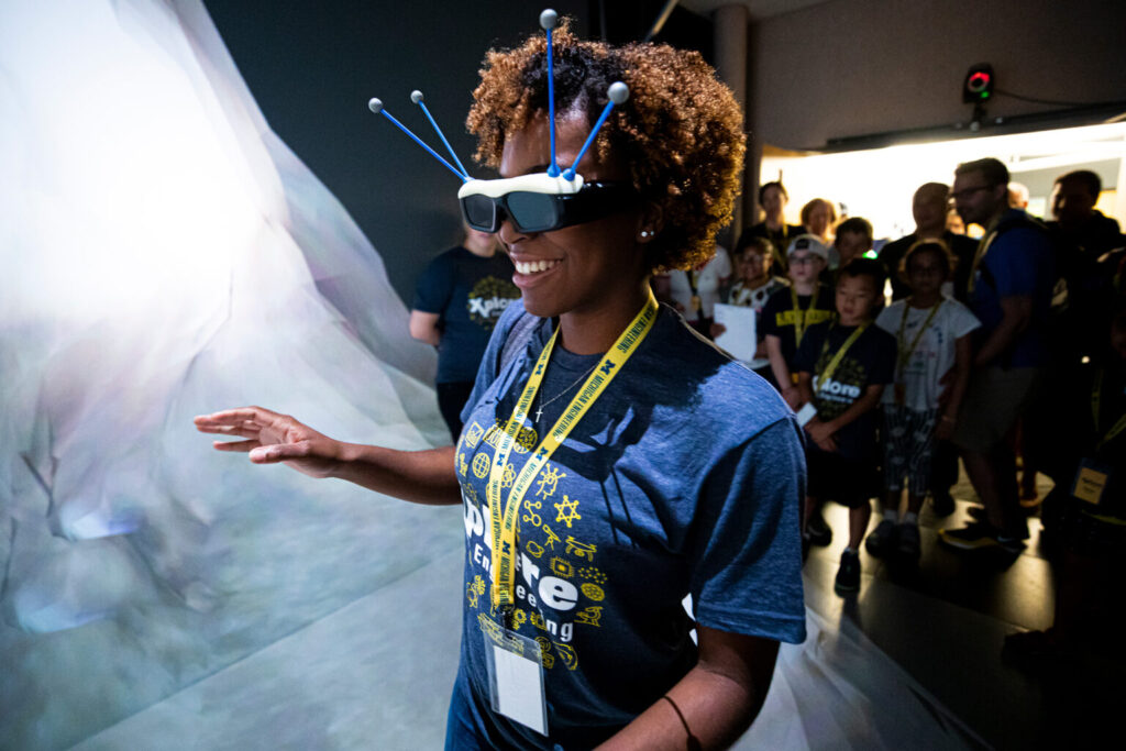 """Prospective students explore the Michigan Immersive Digital Experience Nexus, or MIDEN, the Duderstadt Center's immersive reality space, as part of an """"Explore Engineering"""" event in 2019. (Photo by Joseph Xu, College of Engineering)"""